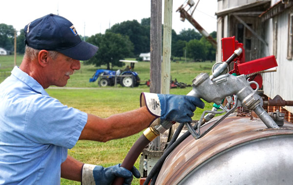 man filling fuel tank for farming